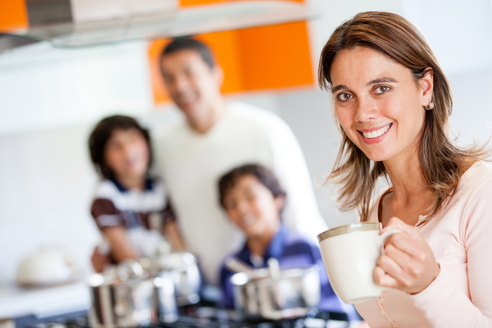 Happy mother holding a cup of coffee in the kitchen